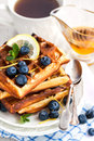 Lemon blueberry waffles with honey zest fresh berries and cup of tea Stock Photos