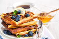Lemon blueberry waffles with honey zest fresh berries and cup of tea Royalty Free Stock Photos