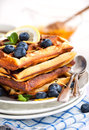 Lemon blueberry waffles with honey zest fresh berries and cup of tea Stock Images