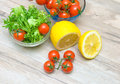 Lemon cherry tomatoes and lettuce friese on a wooden table horizontal photo Royalty Free Stock Image