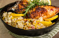 Lemon chicken with rice and roasted corn cast iron skillet seasoned rosemary Stock Image