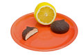 Lemon and chocolate cookie on plate bright yellow isolated white background Royalty Free Stock Photos
