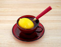 Lemon in cup with water and spoon a large a red filled a atop a wood counter top Stock Image