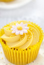 Lemon cupcake with butter cream swirl and fondant flower decorat Royalty Free Stock Photo