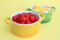 Lemon drops and cherry sours colorful candy dishes with bright red tart in bowls on yellow background Stock Photos