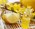 Lemon essence essential oil with yellow flowers transparent bottle with Royalty Free Stock Photos