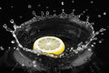 Lemon falls into water on black background Stock Photography