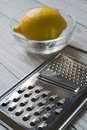 Lemon and grater bowl on a wooden board selective focus over Stock Images