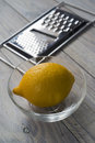 Lemon and grater bowl on a wooden board selective focus over Royalty Free Stock Images