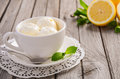 Lemon ice cream in white cup on rustic wooden background Royalty Free Stock Photo