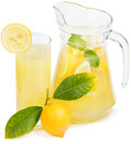 Lemon juice jug and glass with fruit with leaves on white Royalty Free Stock Photo