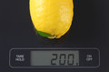Lemon on kitchen scale Royalty Free Stock Photo