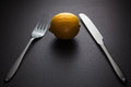 Lemon with knife and fork on black background Stock Photography