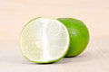 Lemon or lime fruit with half cross section isolated on wooden b other names are in french citrus green key persian kaffir desert Stock Photos