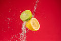 Lemon and lime on red background with water splash Stock Photo