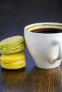 Lemon macaroon and a cup of coffee on wooden background Stock Images