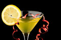 Lemon martini with red streamer on black party Stock Photography