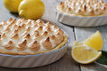 Lemon meringue pie with fresh lemons on wooden background Stock Images