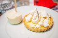 Lemon meringue tart and ice cream a with lavender curd crumbs on top with a vanilla lolly on the side Stock Image