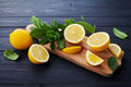 Lemon and mint served on wooden kitchen board on black rustic table, ingredient for summer cocktails and lemonade Royalty Free Stock Photo