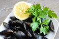 Lemon and mussels raw pieces of with parsley on wooden table Royalty Free Stock Photo