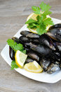Lemon and mussels raw pieces of with parsley on wooden table Stock Photo