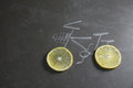 Lemon slice shape wheel of bicycle paint by chalk on black table Royalty Free Stock Photo