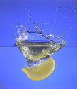 A lemon slice splashing into water with blue background Royalty Free Stock Images