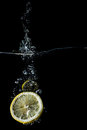 Lemon slices falling into the water close-up, macro, splash, bubbles, isolated Royalty Free Stock Photo