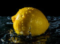 Lemon with splashes falling drops of water close up on black background Royalty Free Stock Photo