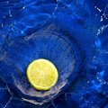 Lemon splashing blue water Royalty Free Stock Photo