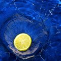 Lemon splashing blue water Royalty Free Stock Photos
