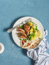 Lemon thyme baked chicken, potatoes and green peas on a white plate on a blue background. Royalty Free Stock Photo