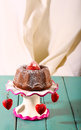 Lemon vanilla mini pound bundt cake with strawberry and icing on top sugar on antic stand red hearts on rustic turquoise Stock Photo