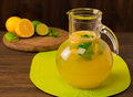 Lemonade with fresh lemon and mint in glass jug on wooden background