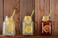 Lemonade and fruit juice glasses on shelf of a rustic kitchen ledge the mason jar style have handles drinking straws Stock Images