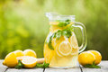 Lemonade in the jug preparation of drink and lemons with mint on table outdoor Stock Photo