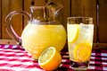 Lemonade and pitcher with sliced lemons on red gingham table cloth Royalty Free Stock Image