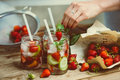Lemonade preparation of three retro glass jars strawberries cucumber and mint on wooden table toned image Stock Photo