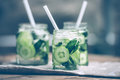 Lemonade three retro glass jars of with cucumber and mint on wooden table toned image Stock Photography