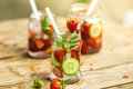 Lemonade three retro glass jars of with strawberries cucumber and mint on wooden table Royalty Free Stock Photo
