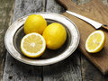 Lemons fresh ripe in the steel plate on wooden board Stock Photos