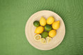 Lemons and limes on a wooden plate on green background Stock Photography
