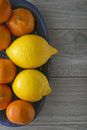 Lemons and mandarin oranges in a blue ceramic tray Stock Photography
