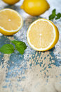Lemons with mint fresh on wooden background empty room for text macro shot Stock Image