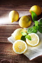 Lemons on a rustic wooden table of wood with sprig of mint Stock Photos