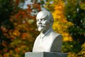 Lenin bust monument with autunm leaves on the background horizontal Stock Photo