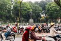 Lenin Park Thong Nhat Park with moving motorcycles in foreground and trees in the park in background at Hanoi, Vietnam