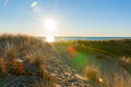 Lens flare as sun bursts over sea and sand Royalty Free Stock Photo