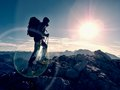 Lens flare defect. Tourist guide on trekking path with poles and backpack. Experienced hiker Royalty Free Stock Photo